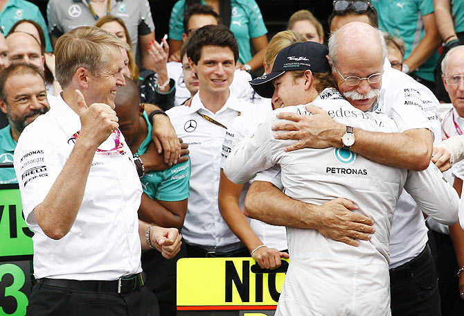 Mercedes Formula One driver Nico Rosberg of Germany embraces Daimler CEO Dieter Zetsche (right) after winning the German F1 Grand Prix at the Hockenheim racing circuit on Sunday