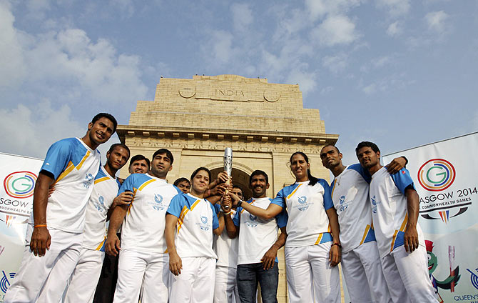 Indian athletes pose as they hold the Commonwealth Games Baton in front of the India Gate in New Delhi