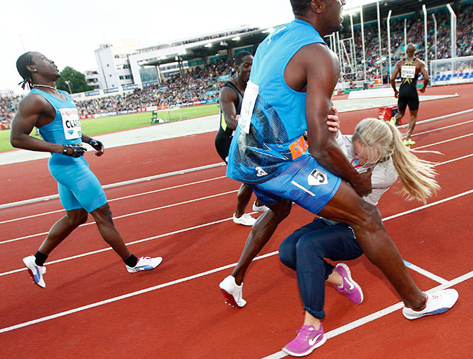 Usain Bolt collides with a flower girl after crossing the finish line