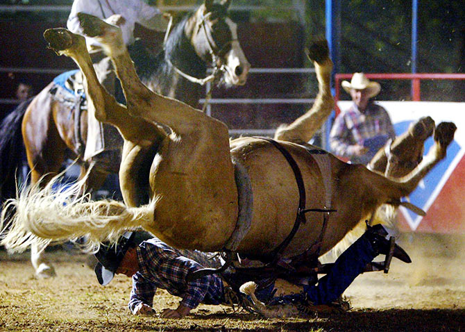 Cowboy Jim Butler is thrown over the head of his bucking horse