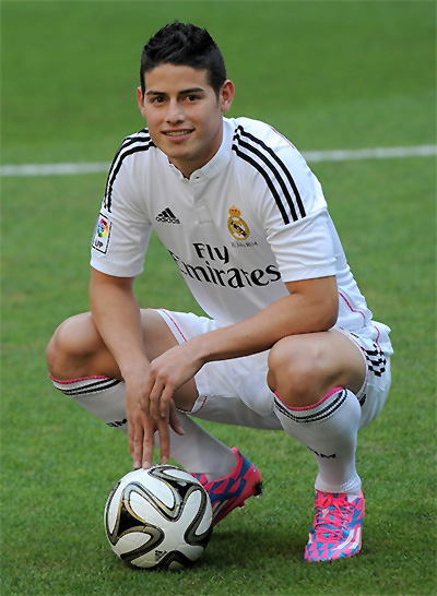 James Rodriguez poses for photographers during his unveiling as a new Real Madrid player at the Santaigo Bernabeu