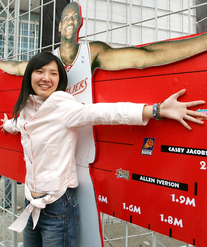 Basketball fan measures her spans against a life-size cutout of National Basketball Association star Lebron James