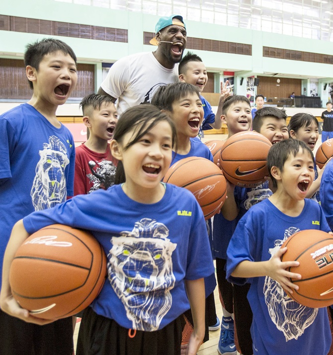 NBA basketball player LeBron James (back centre) of the Cleveland Cavaliers poses for a photo with children after a basketball clinic