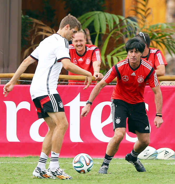 Joachim Loew, right, head coach of Germany battles for the ball with Thomas Mueller