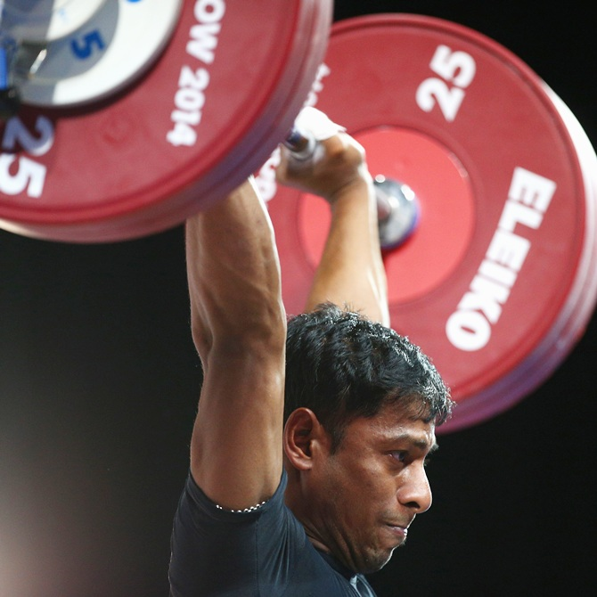 Sukhen Dey of India competes in the Clean and Jerk on his way to winning the gold medal in the men's 56kg weightlifting