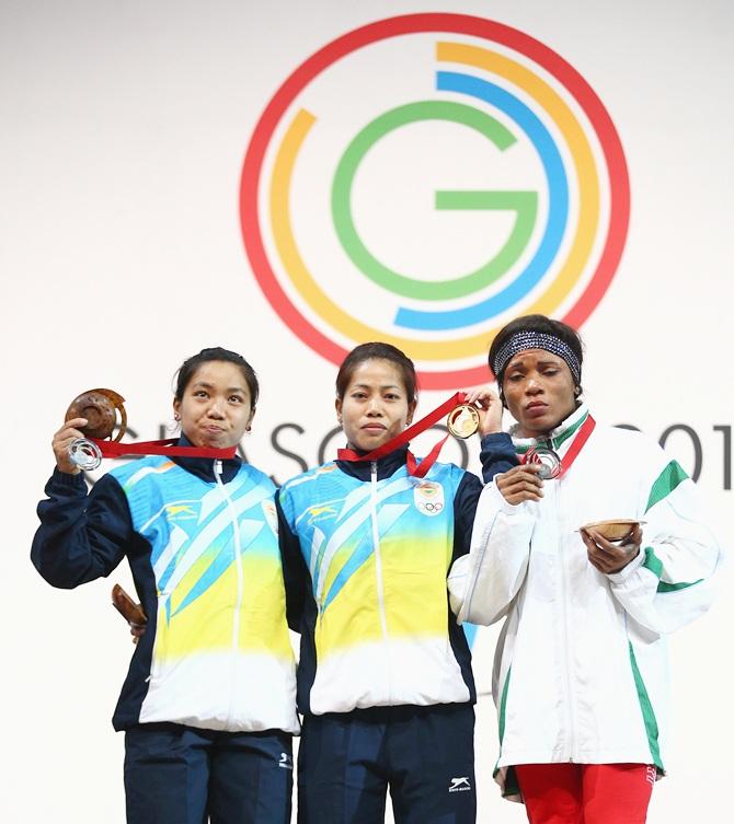 Gold medalist Sanjita Chanu Khumukcham of India (centre), silver medalist Nikechi Opara of Nigeria (right) and bronze medalist Mirabai Chanu Saikhom of India