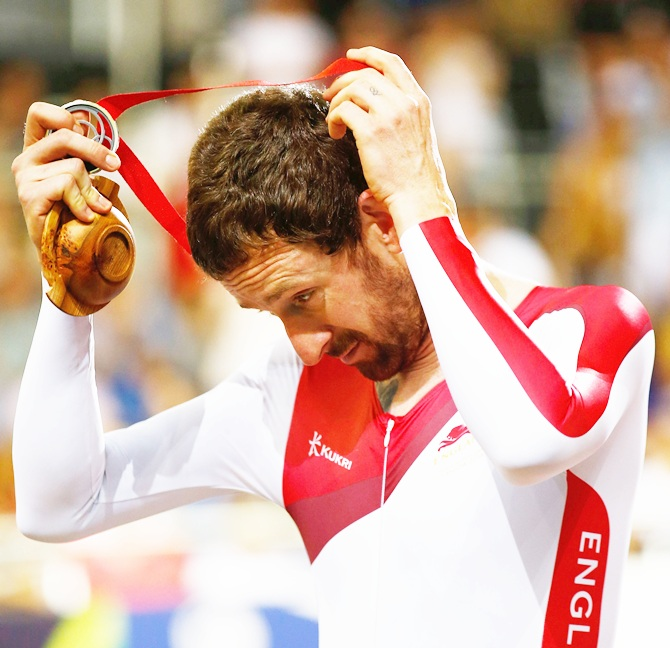 Sir Bradley Wiggins of England takes off his silver medal during the medal ceremony for   the Men's 4000 metres Team Pursuit final at Sir Chris Hoy Velodrome