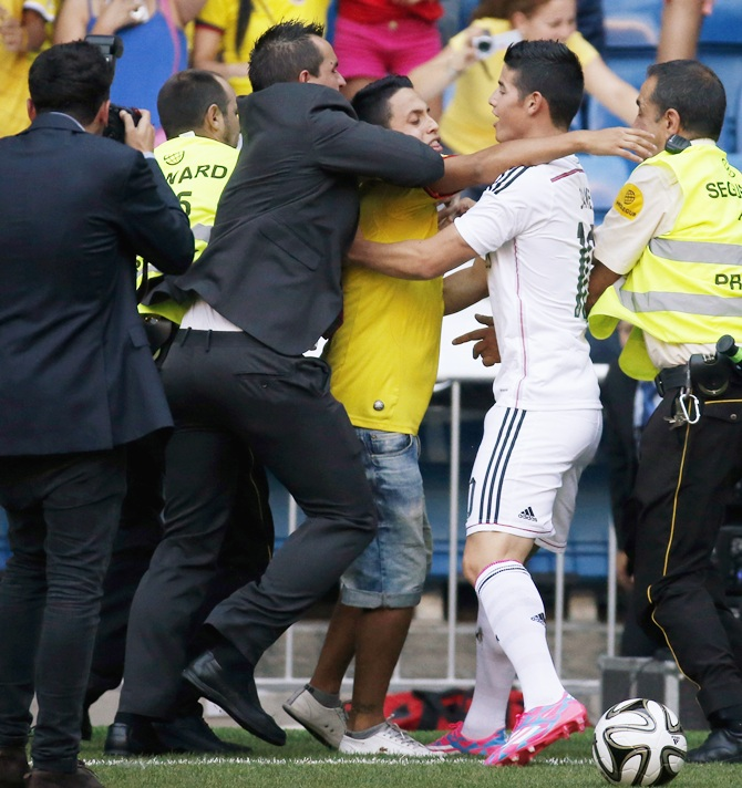 A fan tries to embrace Colombia's soccer player James Rodriguez during   his presentation at the Santiago Bernabeu stadium in Madrid
