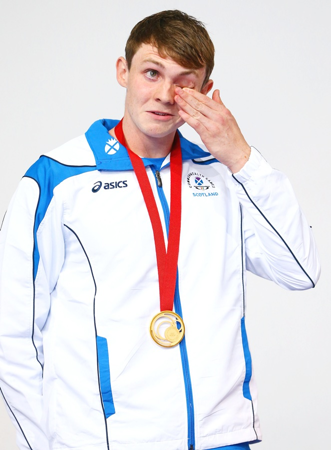 Gold medallist Ross Murdoch of Scotland wipes away tears during the medal ceremony for the   Men's 200m Breaststroke Final at Tollcross International Swimming Centre during day one of the Glasgow 2014 Commonwealth Games