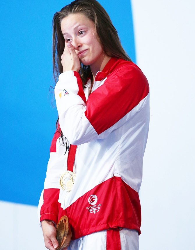 Gold medallist Katerine Savard of Canada wipes away tears