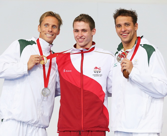 Gold medallist Benjamin Proud, centre, of England poses with silver medallist Roland Schoeman of South Africa and bronze medallist Chad le Clos of South Africa