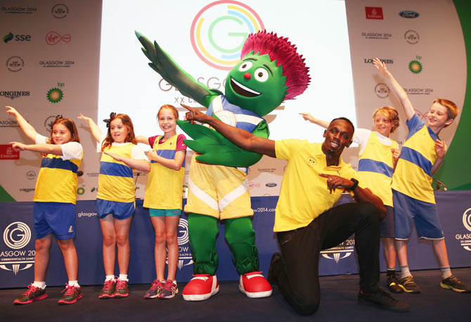 Athlete Usain Bolt of Jamaica (3rd from right) poses with Clyde the mascot and children from Giffnock North Amateur Athletics Club during a photocall at the Main Press Centre at the Glasgow 2014 Commonwealth Games on Saturday