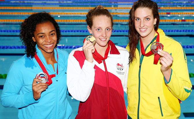 Gold medallist Francesca Halsall of England poses with silver medallist Arianna Vanderpool Wallace of Bahamas and bronze medallist Brittany Elmslie of Australia after the medal ceremony for the Women's 50m Butterfly Final at Tollcross International Swimming Centre on Sunday