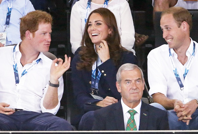 Prince William yells beside his wife Catherine, Duchess of Cambridge, and Britain's Prince Harry, left, as they watch hockey