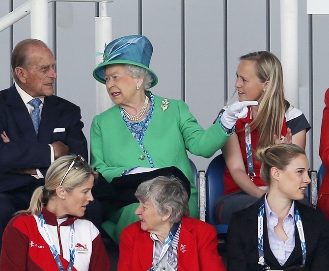 Britain's Queen Elizabeth gestures to her husband Prince Philip, left, as they take their   seats ahead of women's preliminary hockey match between England and Wales