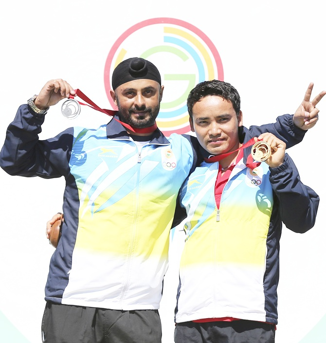 Silver Medalist Gurpal Singh of India and Gold Medalist Jitu Rai of India celebrate on   the podium during Men's 50m Pistol Shooting Final at Barry Buddon Shooting Centre during day five of the Glasgow 2014 Commonwealth Games