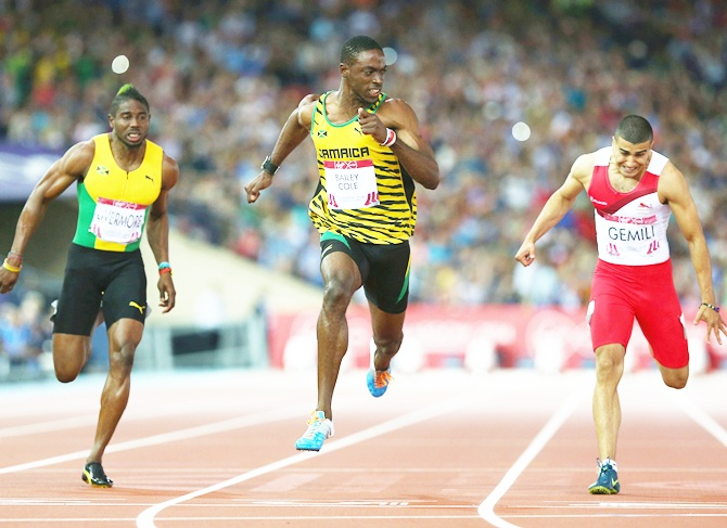 Kemar Bailey-Cole of Jamaica, centre, crosses the line to win gold ahead of silver   medalist Adam Gemili of England, right, in the Men's 100 metres final at Hampden Park during day five of the Glasgow 2014 Commonwealth Games