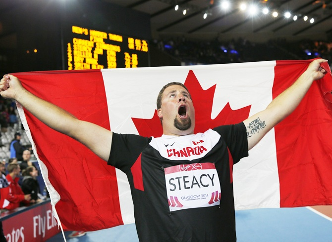 Jim Steacy celebrates with the flag after winning the men's Hammer Throw