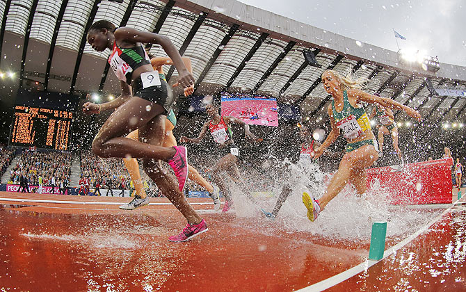 Cherotich Purity Kirui (left) of Kenya competes on her way to a first place finish in Women's 3000m Steeplechase Final at the 2014 Commonwealth Games on Wednesday