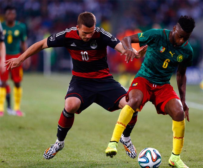 Germany's Lukas Podolski (left) challenges Cameroon's Alexandre Song