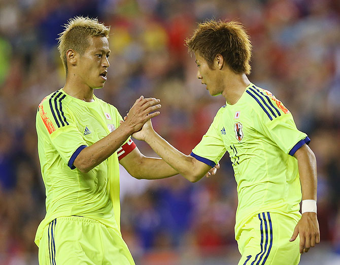 Keisuke Honda of Japan congratulates Yoichiro Kakitani of Japan after scoring a goal during their international friendly against Costa Rica at Raymond James Stadium in Tampa, Florida, on Monday