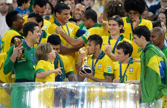 Neymar of Brazil kisses the trophy with his teammates following their victory in 2013