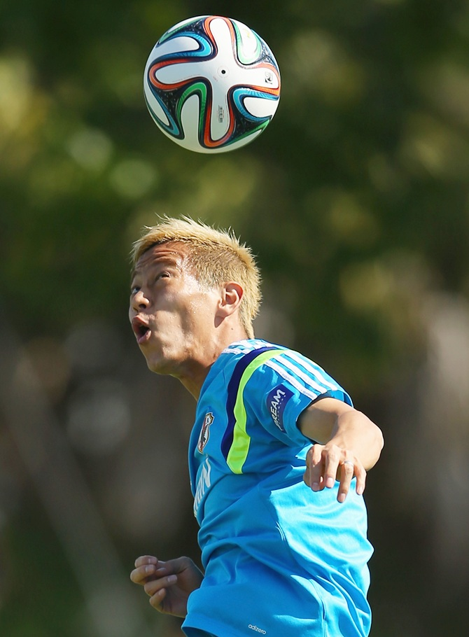 Keisuke Honda heads the ball during a Japan training session