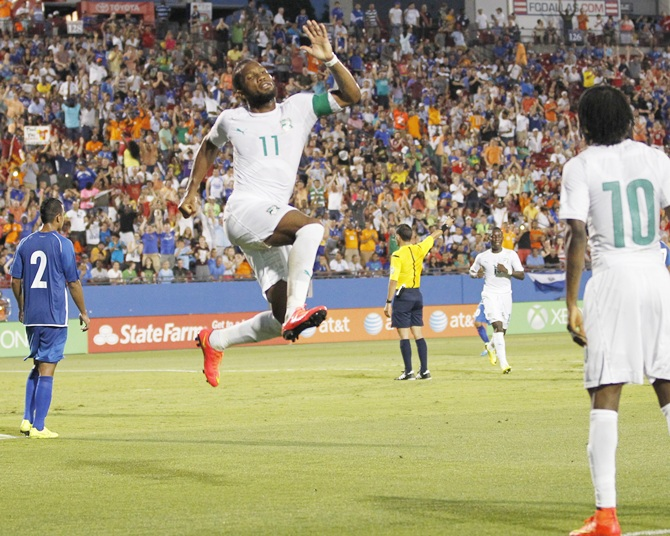 Ivory Coast's Didier Drogba,centre, leaps in the air to celebrate his goal