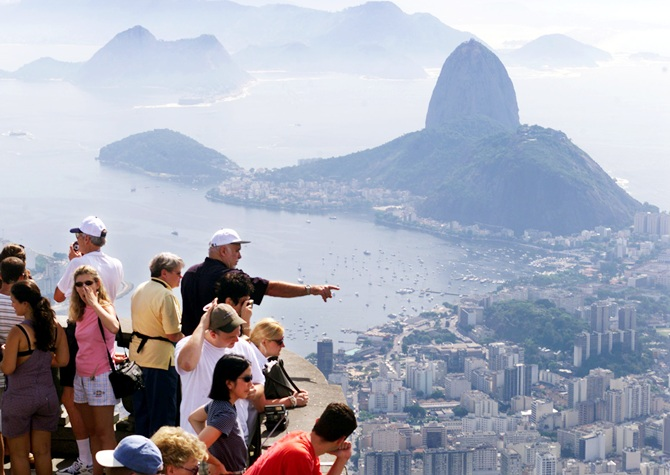 Tourists take in the scene from atop scenic Corcovado mountain in Rio de Janeiro. Sugarloaf mountain and Botafogo beach can be seen in the background