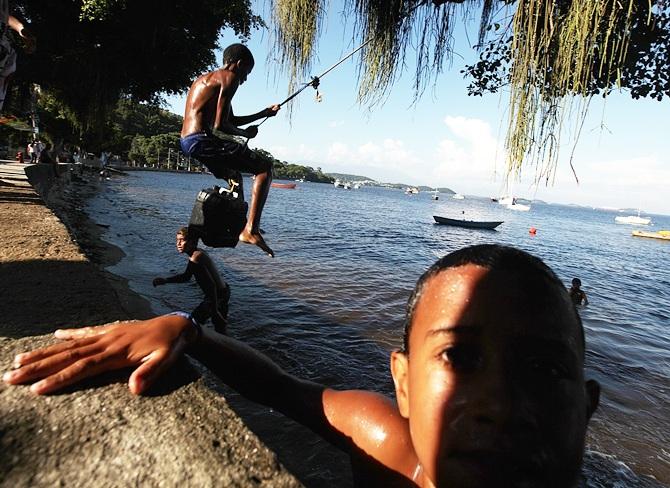 Kids play along the shoreline of the Guanabara Bay in Rio de Janeiro