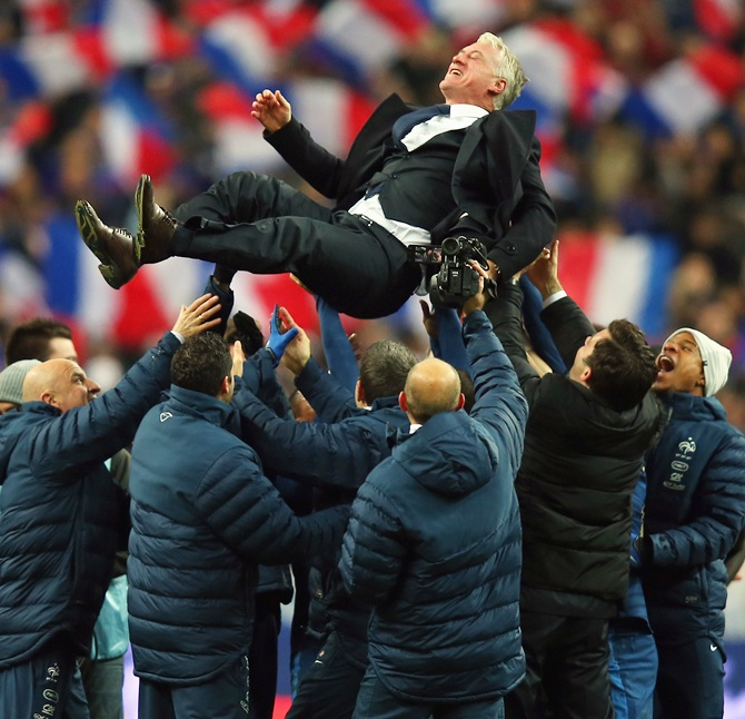 France throw their Coach Didier Deschamps in the air after winning the FIFA 2014 World Cup Qualifier Play-off