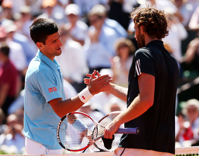Novak Djokovic of Serbia shakes hands with Ernests Gulbis of Latvia