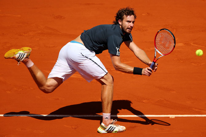 Ernests Gulbis of Latvia returns a shot during his men's singles semi-final against Novak Djokovic