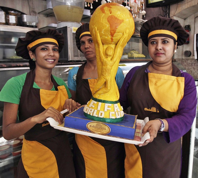 Workers pose with a replica of the one and half feet tall and six kg FIFA World Cup trophy, made from sweets