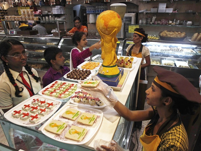 A worker sells sweets next to a replica of the FIFA World Cup trophy, made from sweets in Kolkata