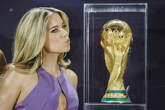 A model poses with the World Cup trophy during a photocall