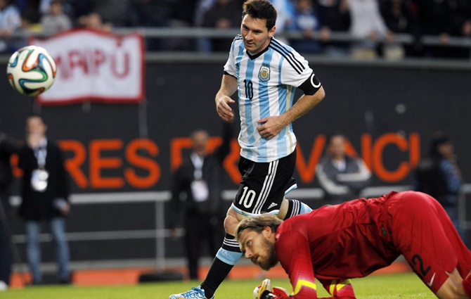 Argentina's Lionel Messi,left, runs past Slovenia's goalkeeper Vid Belec