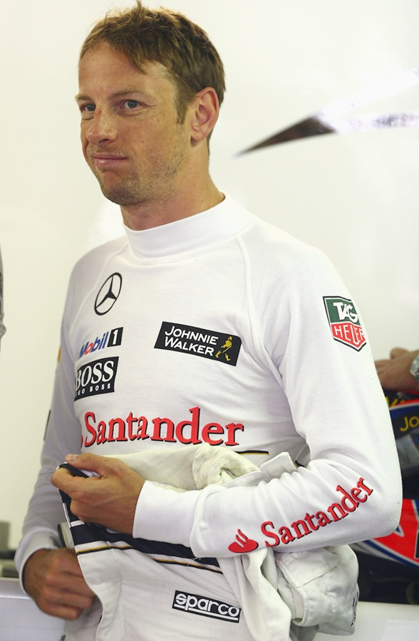 Jenson Button of Great Britain and McLaren looks on in the team garage