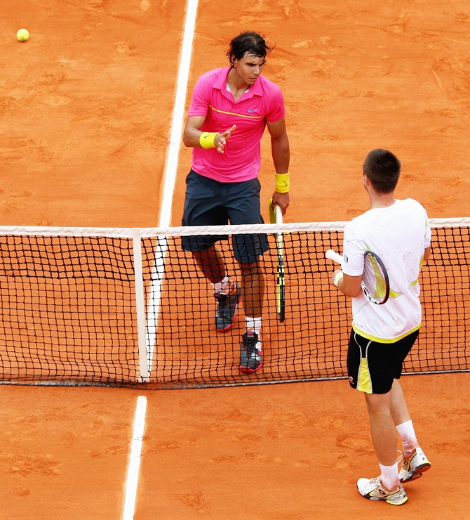 Robin Soderling (below net) of Sweden goes to shake hands with Rafael Nadal of Spain following his victory