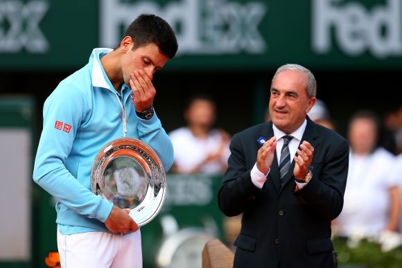 President of the FFT Jean Gachassin applauds Novak Djokovic of Serbia after his defeat in the men's singles final match against Rafael Nadal of Spain on Sunday