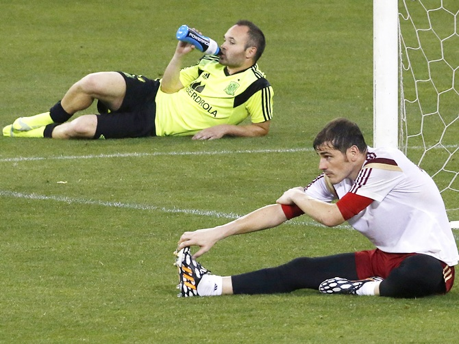 Spain's national soccer team goalkeeper Iker Casillas,right, and teammate Andres Iniesta stretch after a training session