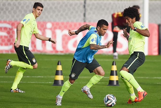 Brazil's Oscar, Daniel Alves and Dante take part in a training session at the squad's Granja Comary training complex, in Teresopolis, 90 km from downtown Rio de Janeiro, Brazil on Monday