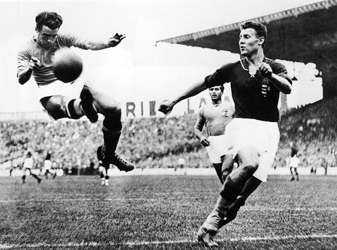 Alfredo Foni (left) of Italy tries to reach a cross during the FIFA World Cup final against Hungary in Paris on June 19, 1938.