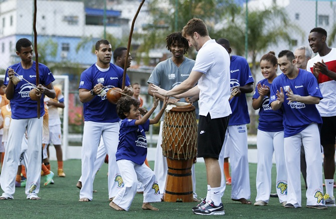England soccer player Adam Lallana shakes hands with a Brazilian boy as teammate Danny Welback looks on during their   visit to the sport complex at the Rocinha slum in Rio de Janeiro