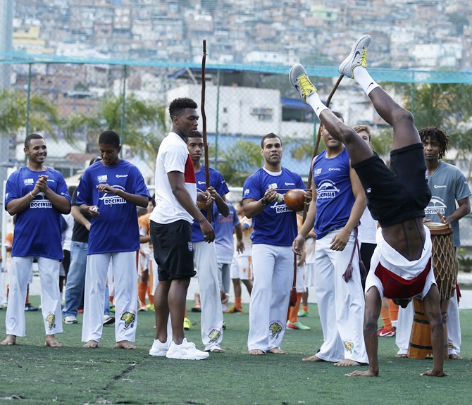 England's Danny Welback,right, performs capoeira as teammate Daniel Sturridge looks