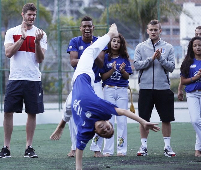 A Brazilian dancer performs Capoeira as England soccer players Fraser Forster and Jack Wilshere look on