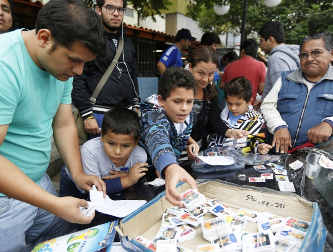 People exchange stickers from the official 2014 FIFA World Cup sticker album along a street in Lima