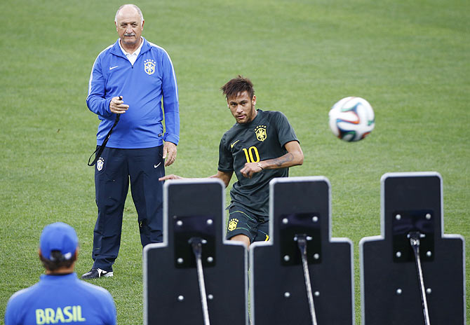 Brazil's national soccer team coach Luiz Felipe Scolari looks on as his striker Neymar practises free kicks during their final practice at the Arena de Sao Paulo in Sao Paulo on Wednesday