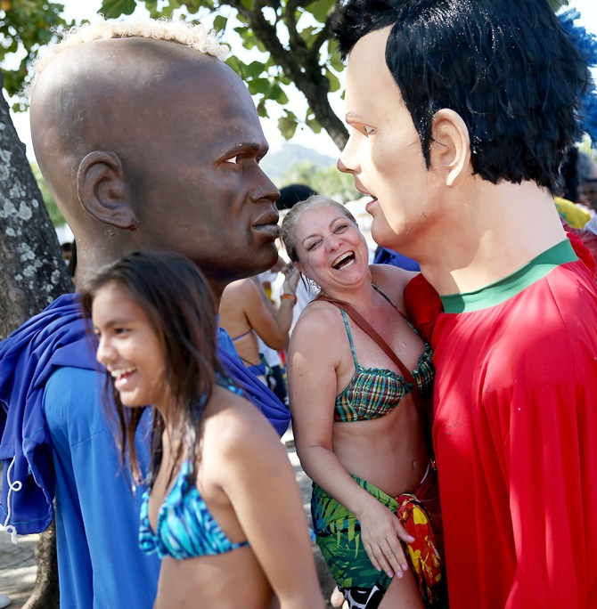 Fans laugh as they stand among large puppets in the likeness of soccer players