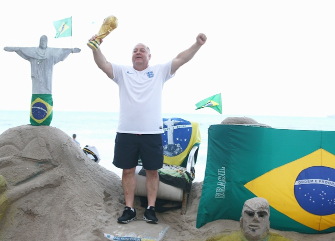 An England fan holds a replica world cup trophy at Copacabana beach in Rio de Janeiro, Brazil